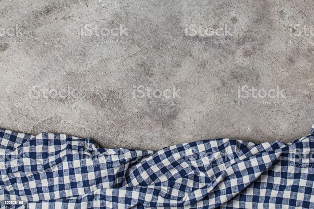 Empty table covered with red checked tablecloth overbrown cement wall...