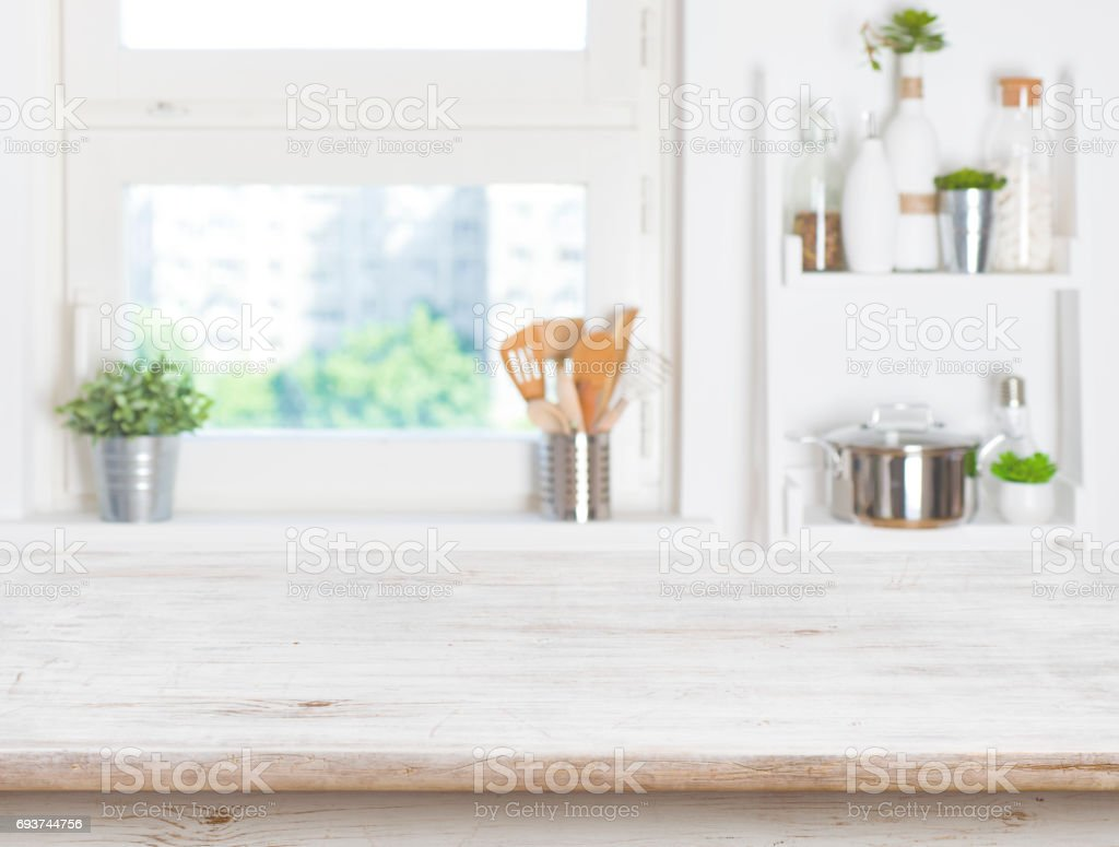 Empty table on blurred background of kitchen window and shelves stock photo