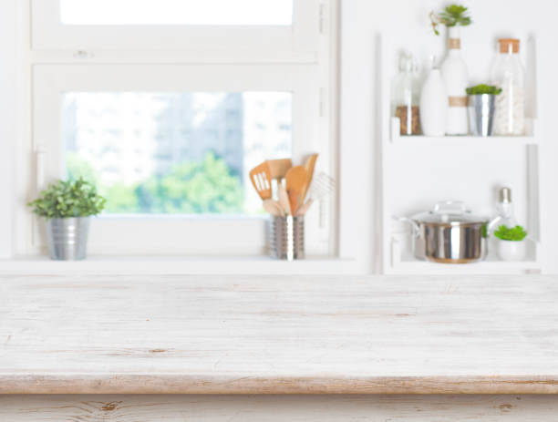 empty table on blurred background of kitchen window and shelves - kitchen counter stock photos and pictures