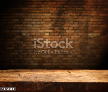 Empty wooden table and brick wall in background