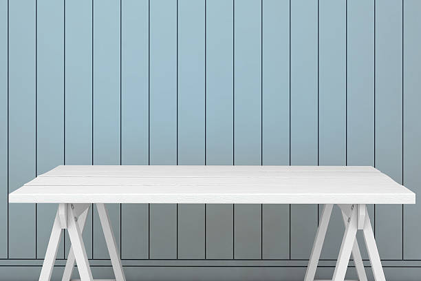 Empty table surrounded by the light blue wall Interior scene showing close up of  empty white vintage style table in front of a light blue striped wall empty desk stock pictures, royalty-free photos & images