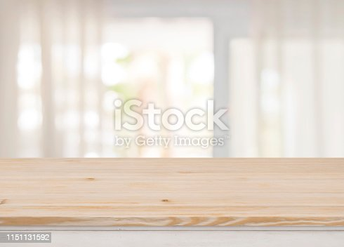 Empty table top on blurred view through abstract curtained window