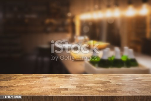 862429776 istock photo Empty table top with dark restaurant kitchen blurred in the background. 1128247568