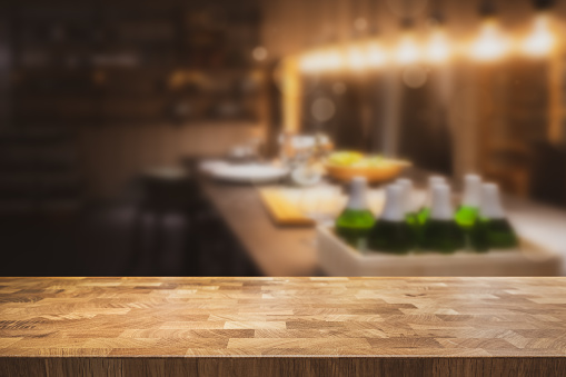 593305530 istock photo Empty table top with dark restaurant kitchen blurred in the background. 1128247568
