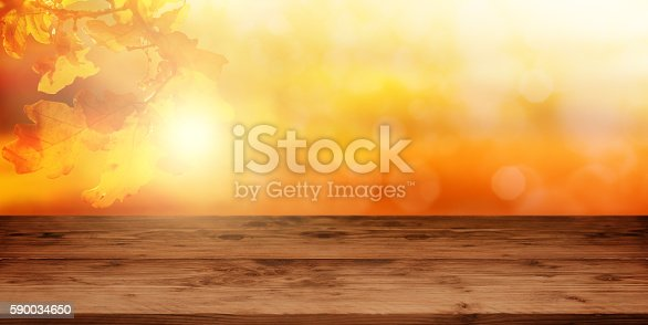 Empty wooden table in front of a autumn background in orange and gold tones
