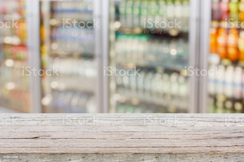 Empty table with blur supermarket refrigeratorr background stock photo