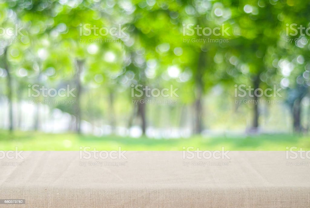 Empty table with linen tablecloth over blur park with bokeh background, food and product display montage royalty-free stock photo