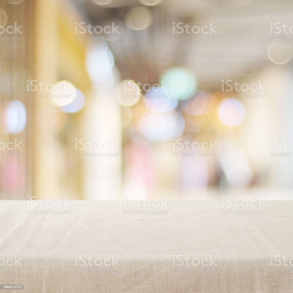 Empty table with linen tablecloth over blurred store with bokeh background, product display montage royalty-free stock photo