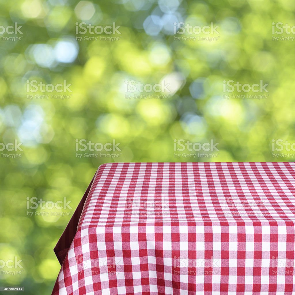 Empty table with tablecloth on green background stock photo