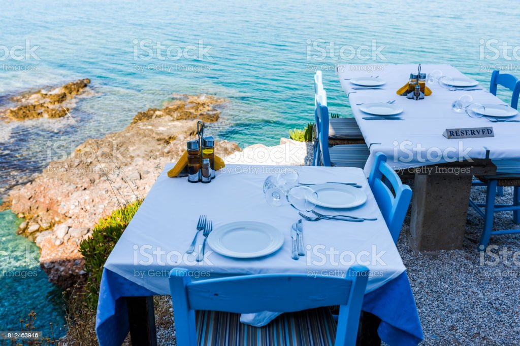 Empty tables of the restaurant on a cliff with an inscription reserved stock photo