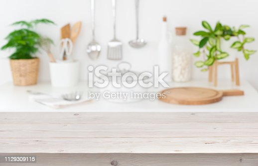 923629650istockphoto Empty tabletop over blurred kitchen cooking place for product display 1129309115
