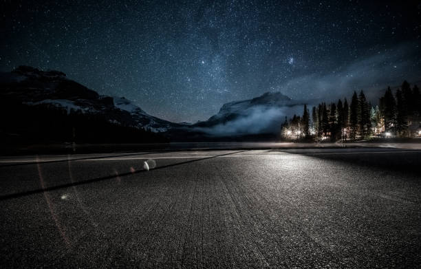empty tarmac road under milky way by Emerald Lake in Yoho national park empty tarmac road under milky way by Emerald Lake in Yoho national park,British Columbia, Canada. emerald lake stock pictures, royalty-free photos & images