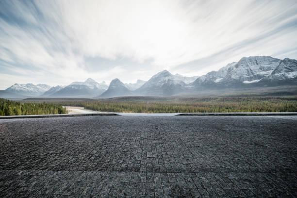 Leere Asphaltstraße mit dramatischer Landschaft im Hintergrund – Foto