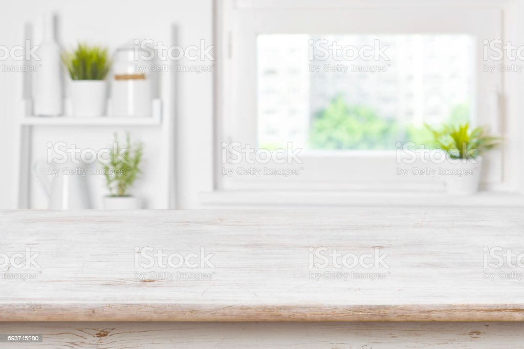 Empty textured wooden table and kitchen window shelves blurred background stock photo