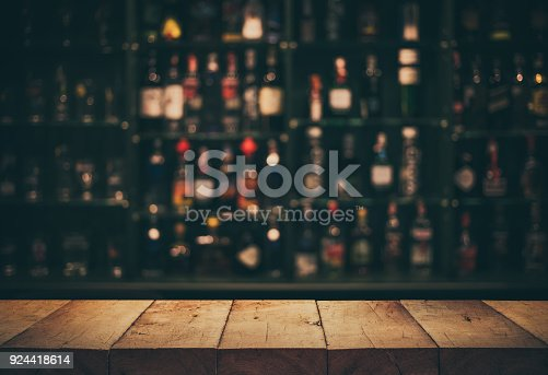 istock Empty the top of wooden table with blurred counter bar and bottles Background 924418614