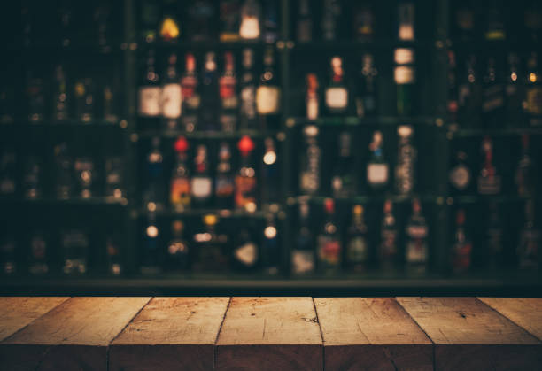 Empty the top of wooden table with blurred counter bar and bottles Background stock photo