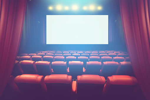 empty theater auditorium with blank screen or movie cinema with red seats before show time