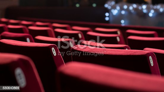 Empty theater with red chairs. Rear view.