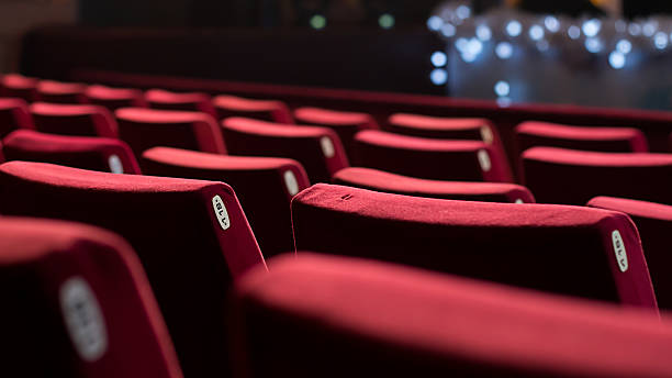 Empty Theater Chairs Empty theater with red chairs. Rear view. seat stock pictures, royalty-free photos & images