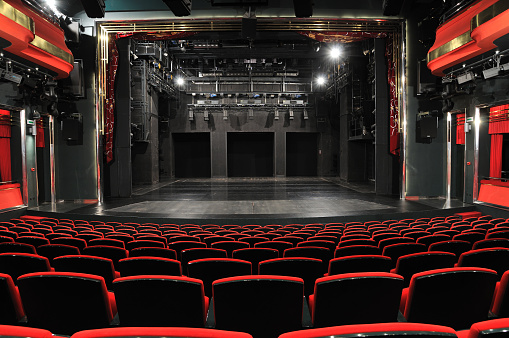 Empty theater with red seats and black stage.