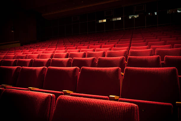 empty theatre with red seats in low light - seat stock photos and pictures