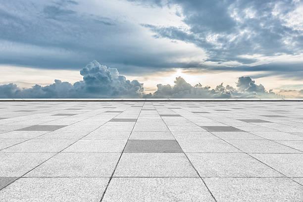 empty tiled floor with cloudy sky stock photo