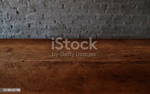 834157738istockphoto Empty top of wooden table or counter isolated on rustic brick Texture background. For product display 1018545798