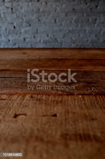 834157738istockphoto Empty top of wooden table or counter isolated on rustic brick Texture background. For product display 1018545800