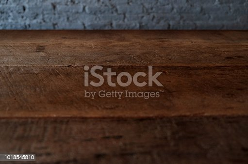 834157738istockphoto Empty top of wooden table or counter isolated on rustic brick Texture background. For product display 1018545810