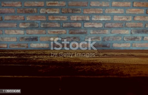 642100994istockphoto Empty top of wooden table or counter isolated on rustic brick Texture background. For product display 1139559088