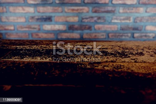 642100994 istock photo Empty top of wooden table or counter isolated on rustic brick Texture background. For product display 1139559091