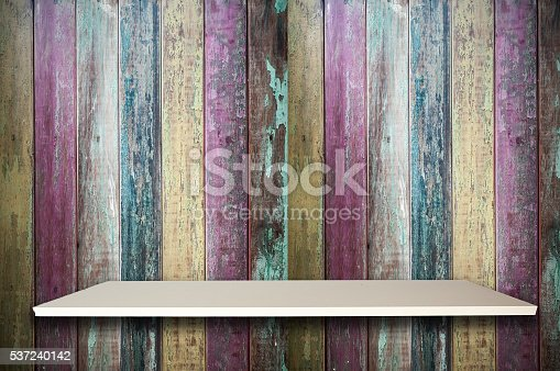471504772 istock photo Empty top white shelves and colorful old wooden background 537240142
