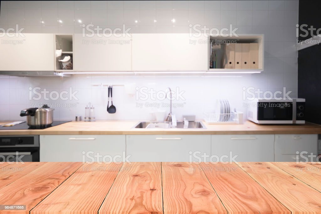 Empty top wooden table and blurred on blur kitchen interior background. For present your products display. royalty-free stock photo