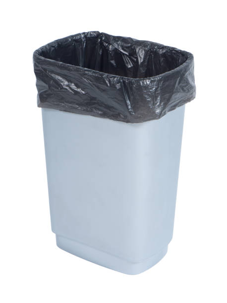 Empty trash container with black plastic bag on white background stock photo