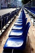 Cobalt blue plastic chairs covered with water drops after rain. Empty tribunes seats in summer town. Morning light.