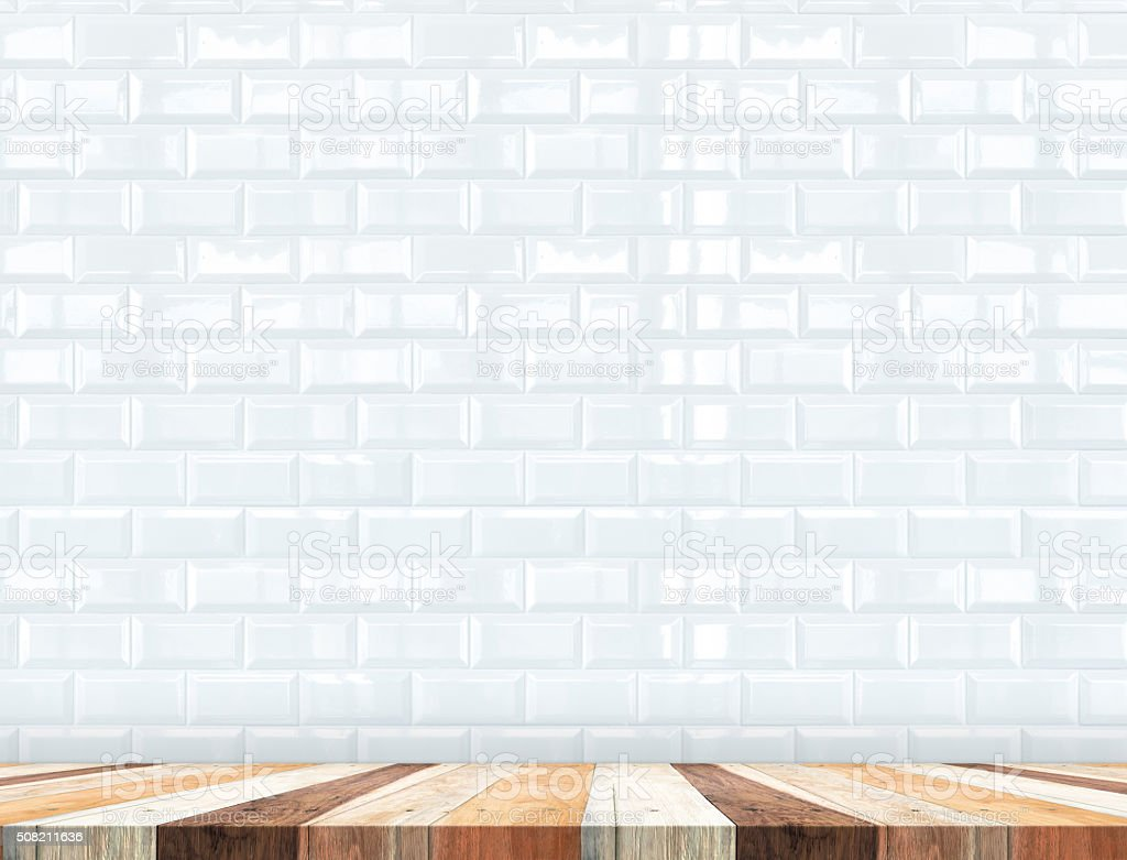 Empty tropical wood table top with white tiles wall stock photo