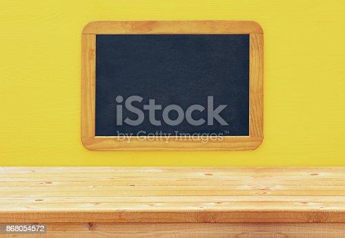 istock Empty vintage blackboard on wooden background 868054572