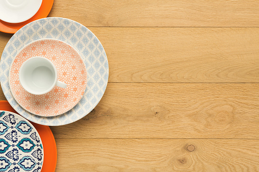 Empty vintage plates and coffee cup on natural wood, top view