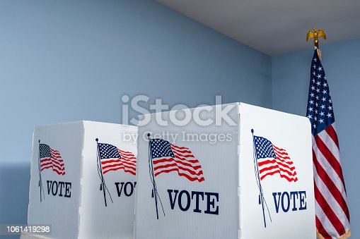 Empty portable voting booths with an American flag decal and the word