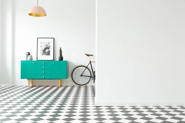 Mur vide et turquoise armoire avec décorations debout à côté d'un vélo dans un décor de couloir avec sol en damier. Un lieu pour votre affiche ou meubles - Photo