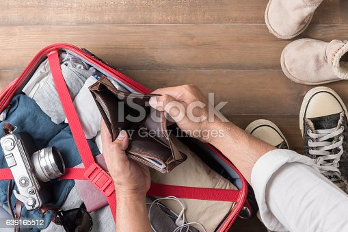 istock Empty wallet in the hand man on Travel accessories  background 639165512