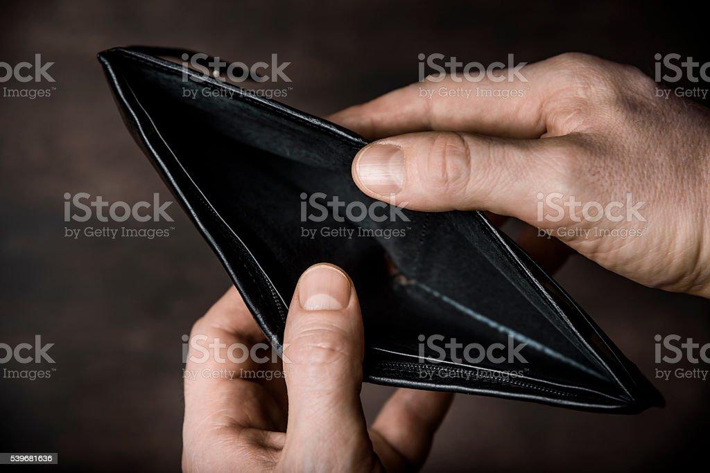 Man opens empty wallet. No money concept.