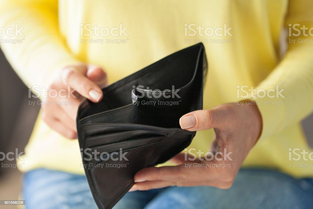 Woman looking at his empty leather wallet in home