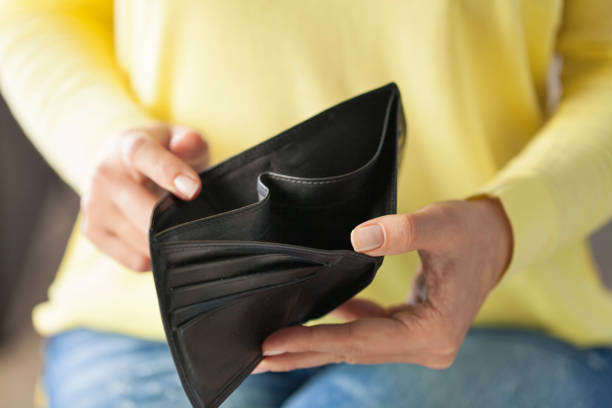 Empty wallet Woman looking at his empty leather wallet in home empty wallet stock pictures, royalty-free photos & images