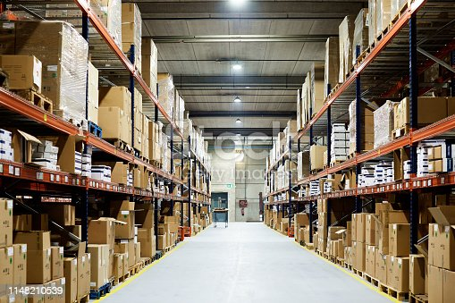 istock Empty warehouse, view down the asile with shelves and boxes. 1148210539