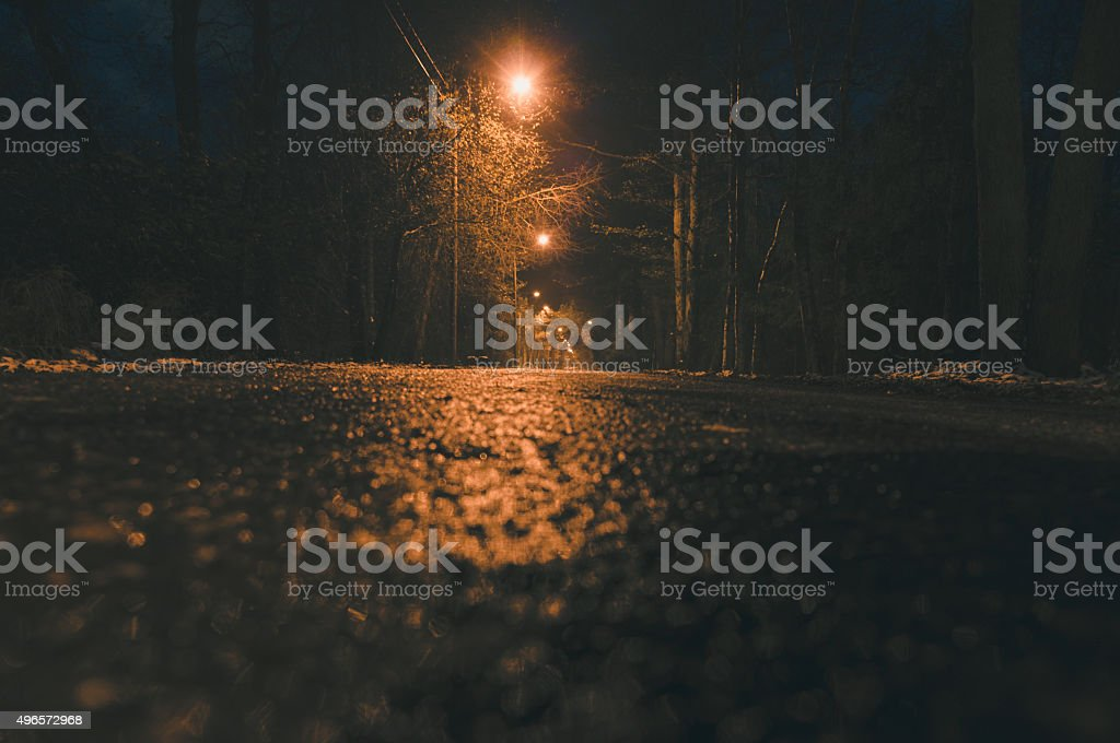 Empty wet asphalt road and lamppost lights at night stock photo