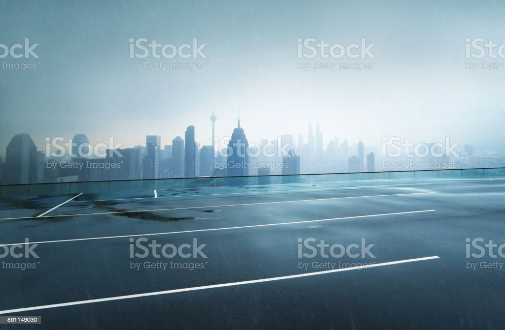 Empty wet asphalt road with foggy city skyline background , raining day . stock photo