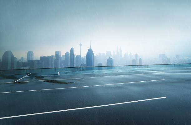 empty wet asphalt road with foggy city skyline background , raining day . - wet stock pictures, royalty-free photos & images
