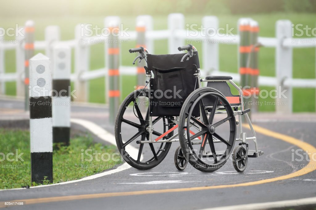 Empty wheelchair across the road in park stock photo