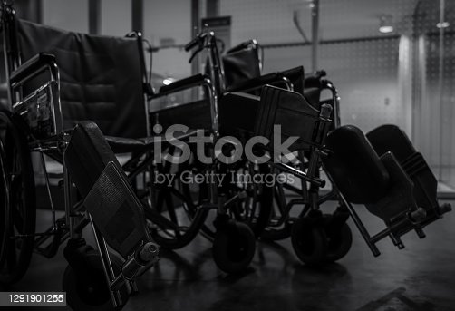 Empty wheelchair in hospital at night for service patient and disabled people. Medical equipment in hospital for assistance handicapped old people. Chair with wheels for patient care in nursing home.